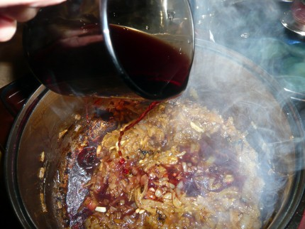 Pour red wine over the caramelized onions